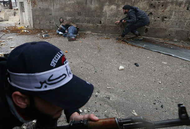 Rebel fighters lie on the ground after being shot by sniper fire during heavy fighting in the Ain Tarma neighborhood, Damascus. | Goran Tomasevic, Reuters