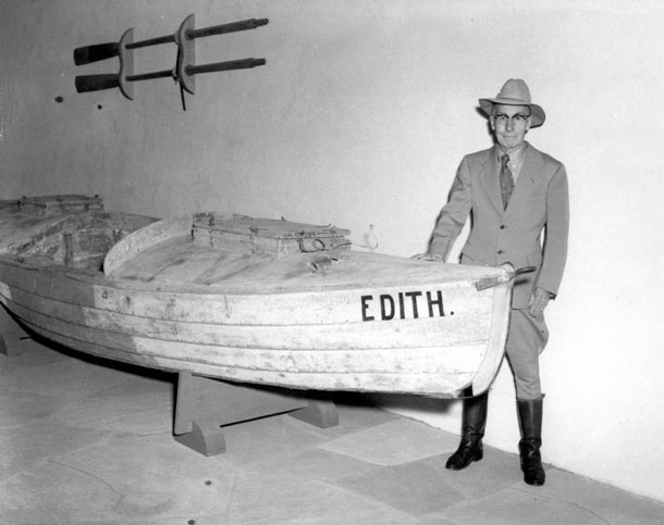 "Symbol of heroism: Emery Kolb posing in front of the boat ""Edith"" he used for the ""big trip."" The scow was custom-made and had to be repaired several times during the trip because of damages caused by the rapids. Emery Kolb, here in May 1959, ran the photo studio until his death in 1976. 