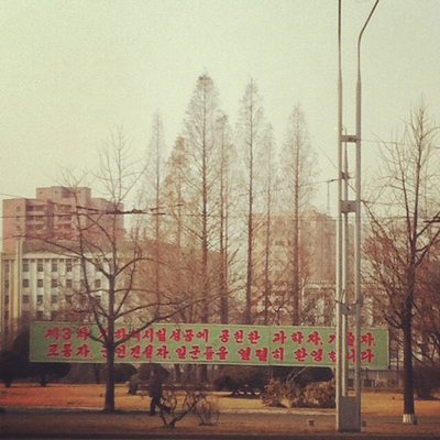 In what's considered to be the first photo posted live from North Korea on Instagram, a man walks in Pyongyang under a roadside banner referring to North Korea's controversial Feb. 12 nuclear test. | Jean H. Lee / AP Photo