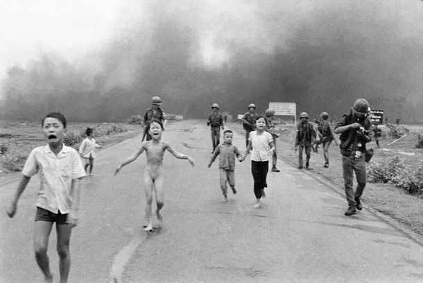 The Original: The photo shot by photographer Nick Út shows a slightly different perspective. His colleague calmly changes a roll of film as Kim Phúc runs passed him. The napalm clouds in the back look less threatening. | AP